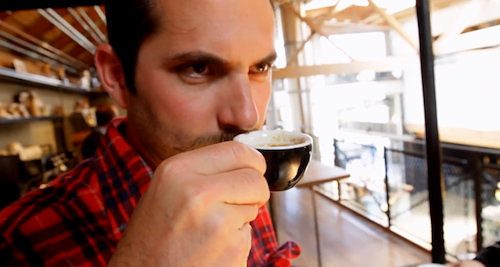 A man drinking a small cup of coffee