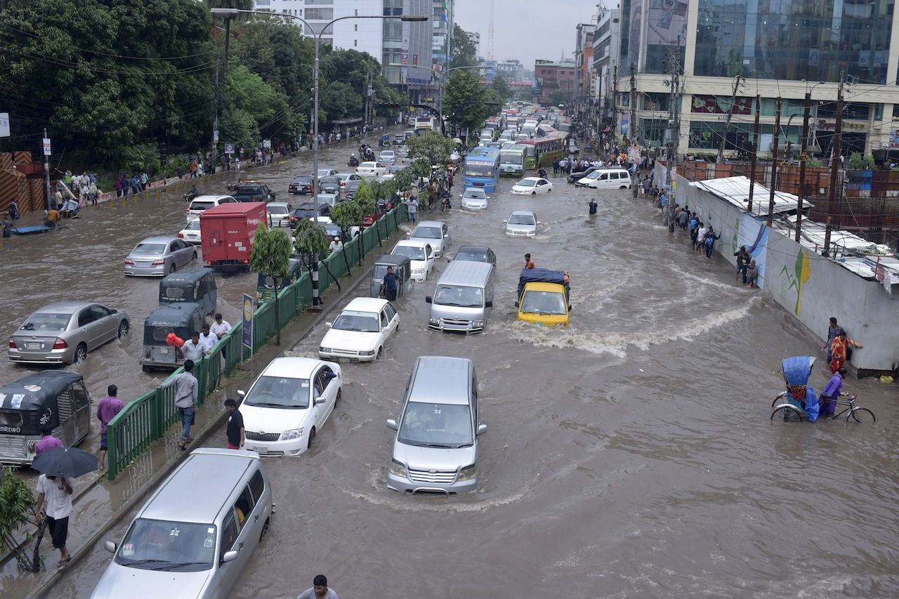 Vehicles trying to drive through a flooded street in Dhaka