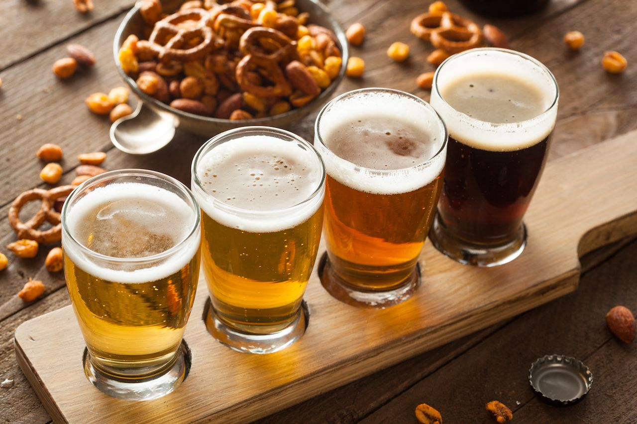flight of beer with pretzels and peanuts