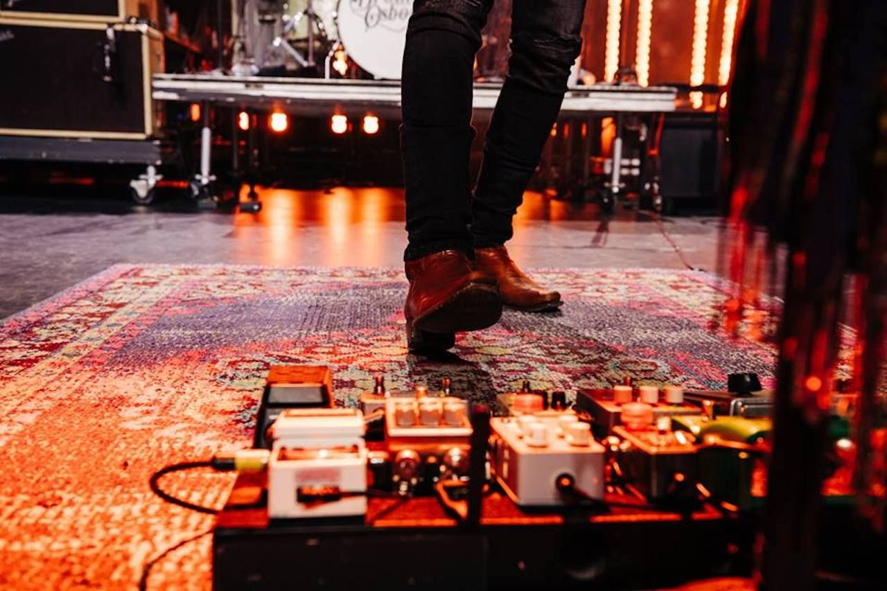 Musician in front of a stage with foot pedals